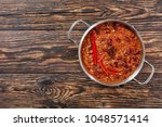 a pot of hot delicious chili... | Shutterstock . vector #1048571414