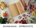 young woman is holding cookbook ... | Shutterstock . vector #1048614131