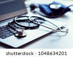 stethoscope on laptop keyboard... | Shutterstock . vector #1048634201