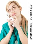 calling female doctor looking up, white background - stock photo