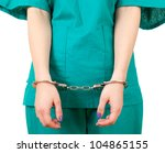 crime in medicine - lady doctor in green uniform with handcuffed hands, focus on foreground, white background - stock photo
