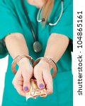 bribe in medicine - lady doctor in green uniform with handcuffed hands with money, focus on foreground, white background - stock photo