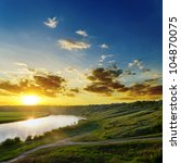 sun over river with dramatic sky - stock photo