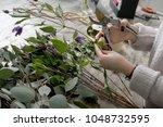 the hands of florist against... | Shutterstock . vector #1048732595