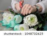 the hands of florist against... | Shutterstock . vector #1048732625