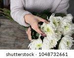 close up of flowers in hands of ... | Shutterstock . vector #1048732661