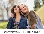 two happy young women friends... | Shutterstock . vector #1048751684