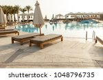 swimming pool with chaise... | Shutterstock . vector #1048796735
