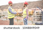 Small photo of Builders on residential construction site making a deal - Happy workers are satisfied of their plan - Dealing, real estate, engineer, industrial and building houses concept