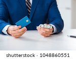businessman holding dollar... | Shutterstock . vector #1048860551