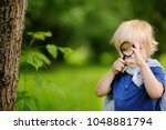 funny kid exploring nature with ... | Shutterstock . vector #1048881794