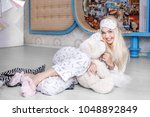 a beautiful girl hugs a bag in... | Shutterstock . vector #1048892849