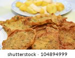 closeup of a plate of spanish shrimp cakes and patatas bravas in the background - stock photo