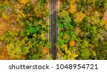 aerial view of road in autumn... | Shutterstock . vector #1048954721