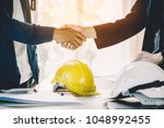 Small photo of Successful deal, male architect shaking hands with client in construction site after confirm blueprint for renovate building.