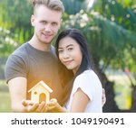 man and woman holding a house... | Shutterstock . vector #1049190491