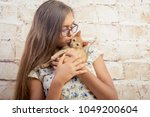 Stock photo girl with a favorite kitten young beautiful girl is holding a red kitten lovely portrait of a 1049200604