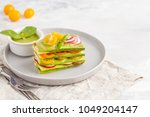 Stock photo raw zucchini lasagna with vegetables and pesto sauce light background vegetarian raw diet concept 1049204147