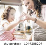 young mother cooking with her... | Shutterstock . vector #1049208209