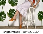 stylish girl sits on a white... | Shutterstock . vector #1049272664