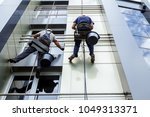 Two industrial climbers are washing, cleaning facade of a modern office building. Cloudy sky in background.