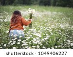 beautiful girl collects daisies ... | Shutterstock . vector #1049406227