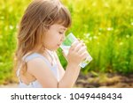 the child holds a glass of... | Shutterstock . vector #1049448434