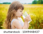 the child holds a glass of... | Shutterstock . vector #1049448437