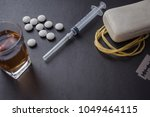 a glass with whiskey  drugs  a... | Shutterstock . vector #1049464115