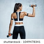 strong woman working out with... | Shutterstock . vector #1049478341