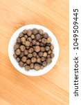 Small photo of Dried whole allspice on a wood background