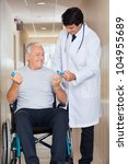 Happy young doctor giving hand weights to the senior man sitting in a wheelchair at hospital - stock photo