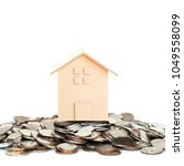 Small photo of House model with money stacks and coins for finance and banking on white background. Concept for mortgage and real estate investment. Investment and saving concept. Baht currency