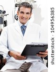 Confident optometrist smiling while holding a clipboard at his clinic - stock photo