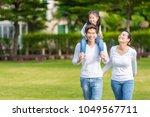 cute asian girl on neck parents ... | Shutterstock . vector #1049567711