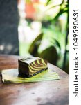 Small photo of Raw mint chocolate spiral mousse cake on a leaf. Green nature background. Gluten-free, wheat-free, dairy-free, sugar-free dessert. Copyspace