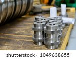 Small photo of Shaft shaft, gear after machining on the lathe and CNC milling machine lies on a wooden rack in the shop.