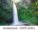 huge fast waterfall hidden in... | Shutterstock . vector #1049716301