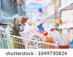 woman doing grocery shopping at ... | Shutterstock . vector #1049730824