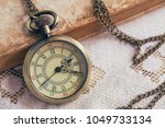 pocket watch and book on lace... | Shutterstock . vector #1049733134