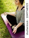 women meditating in grass on...   Shutterstock . vector #1049768525