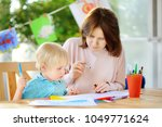 cute little boy drawing and... | Shutterstock . vector #1049771624