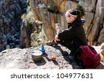 Chinese asian woman sitting and enjoying the view after a hike, trek in the mountains on an adventure tourism holiday camping trip - stock photo
