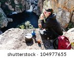 Portrait of an asian chinese backpacker smiling and drinking a mug of coffee while hiking and exploring on a tourist adventure in the wilderness mountains - stock photo