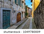 narrow cobblestone street among ... | Shutterstock . vector #1049780009