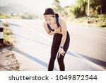 woman chest pain while jogging | Shutterstock . vector #1049872544