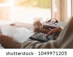 Small photo of Accountant calculating the Saving Account Book and Statement of financial statements at home. Accountancy Concept.