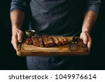 man holding juicy grilled beef... | Shutterstock . vector #1049976614