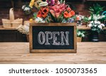 open sign on wooden table among ... | Shutterstock . vector #1050073565