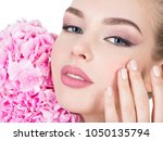 young woman touches cheek by... | Shutterstock . vector #1050135794